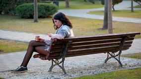 Attractive cute brunette girl sits on bench in city park and drinks hot coffee from which there is steam and writes in phone. Side view, slim attractive cute stock video footage