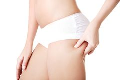 Side view of slim woman checking fat on buttocks Royalty Free Stock Photo