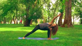 Caucasian sportswoman doing yoga. Side view slim woman practicing asana in park. caucasian girl with long curly hair trains outdoors. nature landscape with green stock video footage