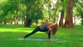 Sportswoman doing asana warrior pose. Side view slim woman practicing yoga in park. caucasian girl with long curly hair trains outdoors. nature landscape with stock footage