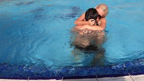 Slow motion of passionate man and woman kissing and hugging while swimming in clean water of pool. Side view slow motion of passionate man and woman kissing and stock video
