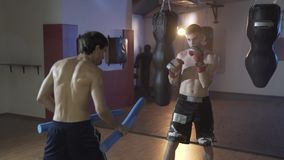 Side view of a slow-motion shot, close-up of a boxer training. The concept of sport, boxing, strength, boxing pear and. Gloves, punch. Exhausting training for a stock video footage