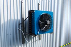Side view of the small blue industrial cooling unit installed on the gray metallic wall of the factory building. Side view of the small blue industrial cooling Royalty Free Stock Photo