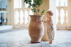 A side view of small toddler girl standing on tiptoes on summer holiday by a flower pot. royalty free stock photography