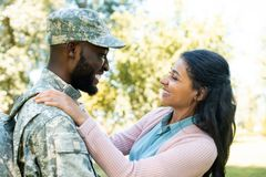 side view of smiling african american soldier in military uniform hugging girlfriend stock photos