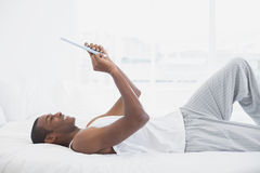 Side view of smiling Afro man using digital tablet in bed Stock Photos