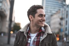 Delighted young man enjoying leisure outside. Side view of smiling attractive male standing on street and looking sideways. He is waiting for his friend with joy Stock Photos