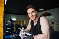 Side view of smiling boxer relaxing in boxing ring Stock Photo