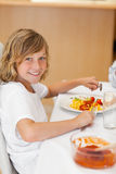 Side view of smiling boy at the dinner table Stock Photography