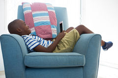 Side view of smiling boy looking at mobile phone while lying on armchair Stock Photo