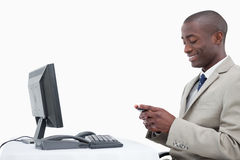 Side view of a smiling businessman sending a text message Stock Photos