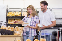 Side view of a smiling casual couple taking a bread Royalty Free Stock Photo