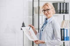 side view of smiling chiropractor in eyeglasses and white coat pointing at human
