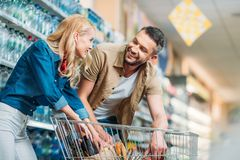 side view of smiling couple checking purchases in shopping cart stock photo