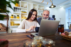 Side view of smiling couple looking at the screen of a laptop at. Low angle of smiling couple looking at the screen of a laptop. Sitting on a chair at the table Royalty Free Stock Photos