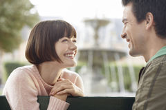 Side View Of Smiling Couple On Park Bench Royalty Free Stock Image