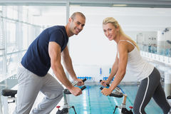 Side view of smiling couple working on exercise bikes at gym Stock Photo