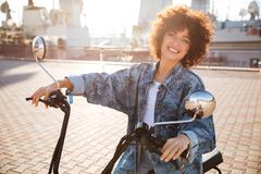 Side view of smiling curly woman sitting on modern motorbike Stock Images