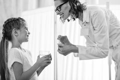 Side view of smiling doctor giving medicines to little girl royalty free stock photo