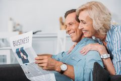 Side view of smiling elderly couple reading business newspaper. At home royalty free stock photo