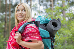 Side view smiling female backpacker in raincoat looking away at forest Stock Image
