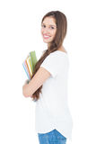 Side view of smiling female college student holding books Royalty Free Stock Photo