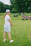 side view of smiling female golf player in cap with golf club standing