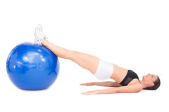 Side view of smiling fit woman lying working out with exercise ball Stock Photos
