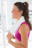 Side view of a smiling fit woman with towel in gym Stock Image