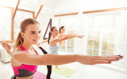 Side view of smiling ladies doing gymnastics. Royalty Free Stock Image