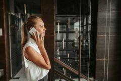 Positive young girl telling on phone indoor royalty free stock photo