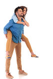 Side view  of  smiling man carrying his girlfriend on back Stock Photo