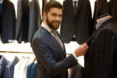 Side view of smiling man choosing a jacket in shop. Side view of smiling bearded man in suit choosing a jacket in shop while looking at camera Stock Image