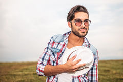 Side view of a smiling  man holding hat to chest Stock Images