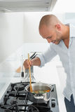 Side view of smiling man preparing food in kitchen Stock Images
