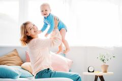 Side view of smiling mother raising laughing little child. While sitting on bed at home royalty free stock photos