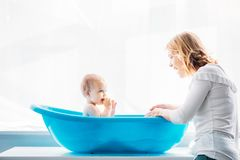 Side view of smiling mother washing her adorable little child. In plastic baby bathtub at home stock photos
