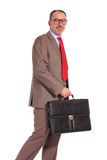 Side view of a smiling old businessman with briefcase walking Stock Images