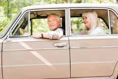 Side view of smiling senior couple sitting in beige. Vintage car stock image