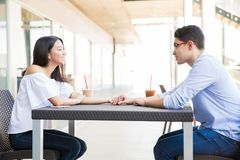 Teenage Couple Dating At Foodcourt In Shopping Mall. Side view of smiling teenage couple dating while sitting at foodcourt in shopping mall Royalty Free Stock Photo
