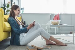Side view of smiling teenage girl. Using smartphone while sitting on carpet with books at home stock images