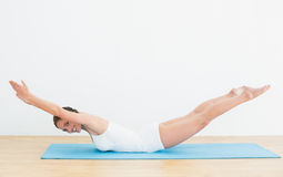 Side view of a smiling woman exercising on mat Stock Image