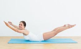 Side view of a smiling woman exercising on mat Stock Photography