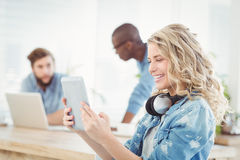 Side view of smiling woman with headphones while using digital tablet Royalty Free Stock Photo