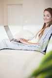 Side view of smiling woman with her laptop sitting on the sofa Royalty Free Stock Photos
