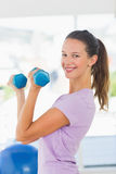 Side view of a smiling woman lifting dumbbell weights Royalty Free Stock Images