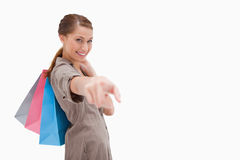Side view of smiling woman pointing with shopping bags Stock Photography