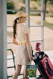 Side view of smiling woman. In polo and cap carrying golf equipment at golf course stock photos