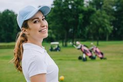 Side view of smiling woman. In polo and cap looking at camera at golf course stock image