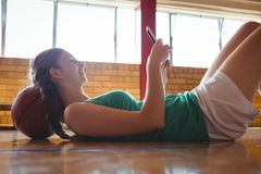 Side view of smiling woman using digital tablet in court. Side view of smiling woman using digital tablet while lying on floor in basketball court Stock Image
